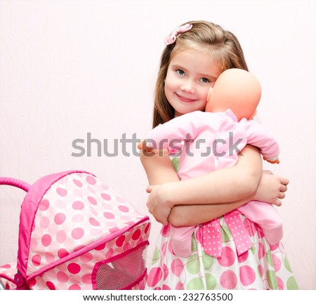 Cute smiling little girl playing with her toy carriage and doll at home - stock photo