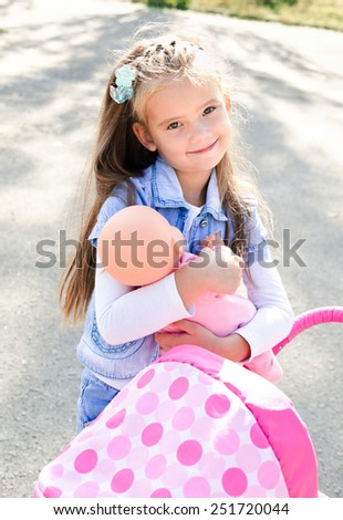 Cute smiling little girl playing with her toy carriage and doll outdoors - stock photo