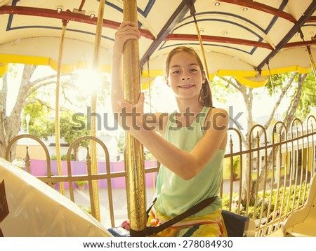 Cute smiling little girl riding on a Carnival Carousel at an amusement park or theme park. Warm afternoon sun in the background - stock photo