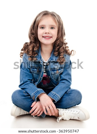 Cute smiling little girl sitting on the floor isolated on a white