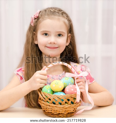 Cute smiling little girl with basket full of colorful easter eggs