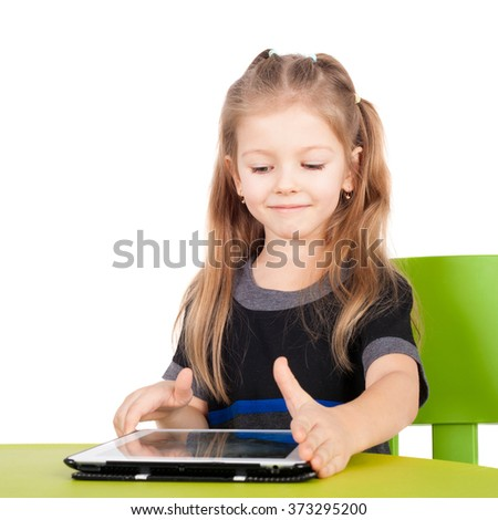 cute smiling little girl with the tablet PC - stock photo
