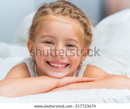 cute smiling little girl woke up in white bed - stock photo