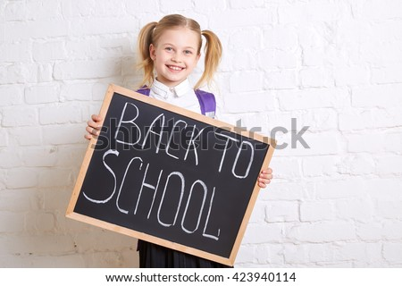 Cute smiling schoolgirl in uniform standing with blackboard and smiling on light  background. Back to school. - stock photo