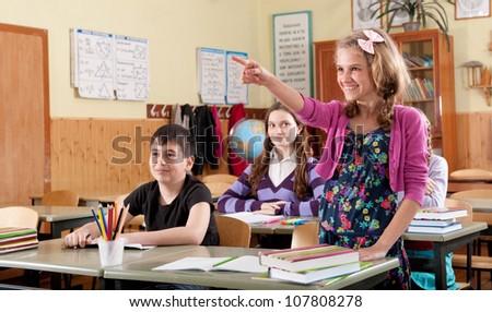 Cute smiling schoolgirl pointing towards a blackboard - stock photo