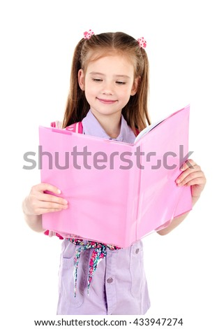 Cute smiling schoolgirl with backpack reading the book isolated on a white background