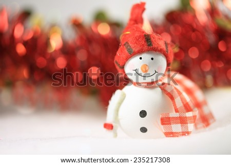 Cute smiling snowman and Christmas ornaments in the background, with copy space - stock photo