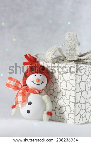 Cute smiling snowman near a white present box.Beautiful winter background with copy space - stock photo