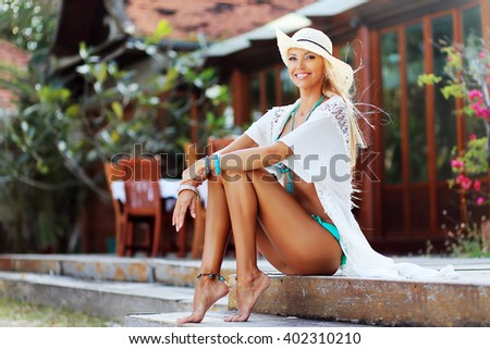Cute smiling tanned girl in hat looking at you - stock photo