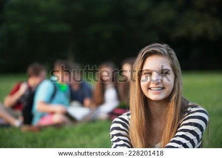 Cute smiling teenage girl with braces sitting outdoors - stock photo