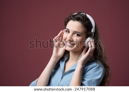 Cute smiling teenager with headphones listening to music - stock photo