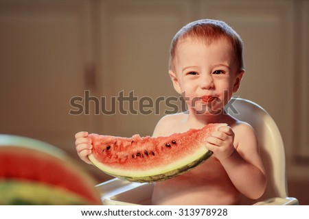 Cute smiling topless little boy with funny face sitting in the child chair and holding big piece of watermelon. Image with toning and selective focus - stock photo