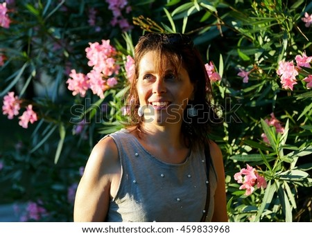 cute smiling woman at sunset and oleander flowers in the background - stock photo
