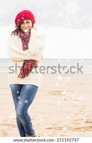 Cute smiling woman in stylish warm clothing at beach against snow falling