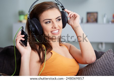 Cute smiling woman lying on couch while listening to music in bright living room