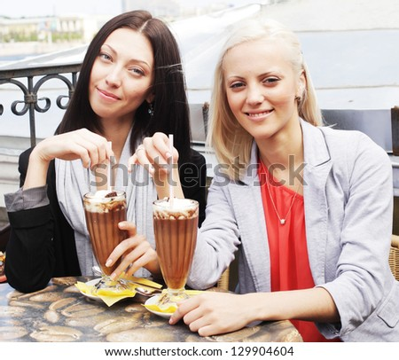 cute smiling women drinking a coffee sitting outside in a cafe bistro