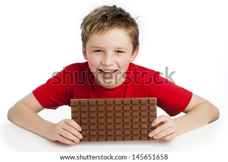 Cute smiling young boy eating a very big bar of chocolate. Wearing a red T-shirt, shot in the studio on a white background. - stock photo