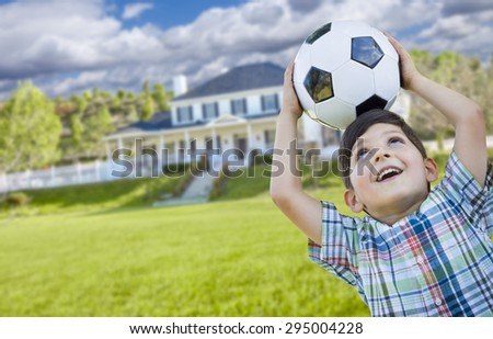 Cute Smiling Young Boy Holding Soccer Ball In Front of Beautiful House. - stock photo
