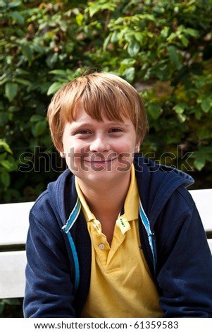 cute smiling young boy sitting on a bench in a garden