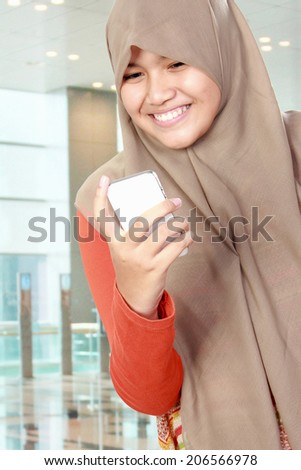 Cute smiling young girl holding a cell phone, text a message - stock photo