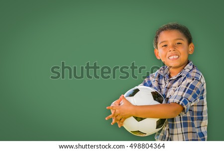 Cute Smiling Young Mixed Race Boy Holding Soccer Ball In Front of Blank Chalk Board.
