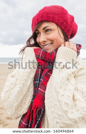 Cute smiling young woman in stylish warm clothing looking away on the beach