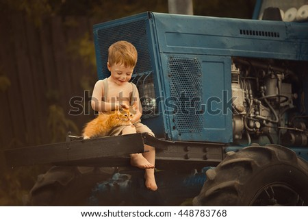 Cute smudgy little boy without t-shirt and shoes, and in pants with suspenders sitting on the tractor  in the countryside and stroking a ginger kitten. Image with selective focus and toning - stock photo