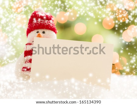 Cute Snowman with Scarf and Hat Next To Blank White Card Over Abstract Snow and Light Background - stock photo