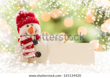 Cute Snowman with Scarf and Hat Next To Blank White Card Over Abstract Snow and Light Background. - stock photo