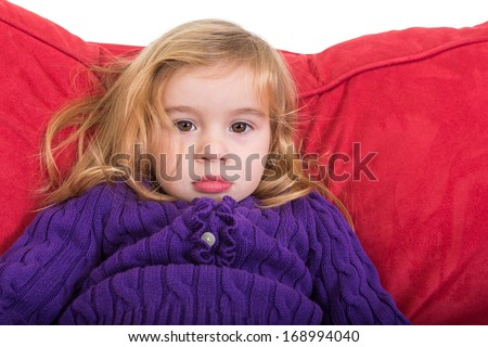 Cute solemn beautiful young girl staring at the camera with a calm expression as she relaxes on a comfortable red cushion in her colourful purple sweater - stock photo