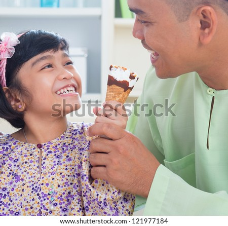 Cute Southeast Asian girl feeding ice cream to father. Malay Muslim family lifestyle - stock photo