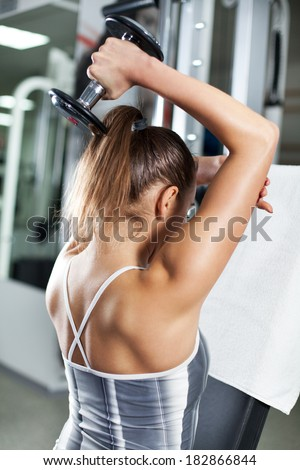 Cute Sporty young woman doing exercise in a fitness center. She is working exercises to strengthen her triceps.