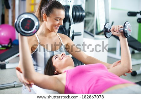 Cute Sporty young woman doing exercise in a fitness center with her personal coach. She is working exercises to strengthen her chest. - stock photo