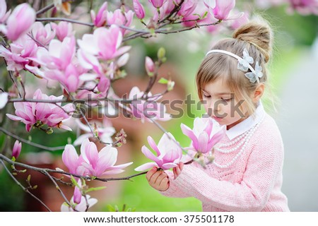 Cute spring  fashion girl under blossom magnolia tree