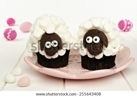 Cute spring sheep cupcakes on pink plate with Easter eggs  - stock photo
