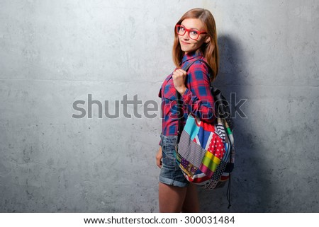 Cute student. Attractive young woman in plaid shirt holding backpack while standing against wall. - stock photo