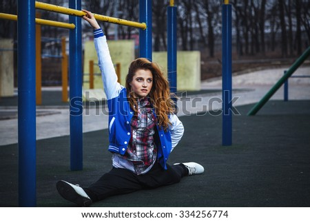Cute student doing gymnastic splits on a deserted open area - stock photo