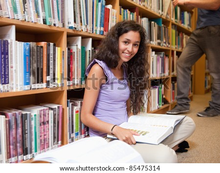 Cute student with a book in a library - stock photo