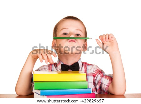 Cute student with books and pencil behind his desk isolated on white background.