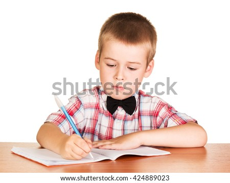 Cute student writes in a notebook sitting at a desk on a white background.