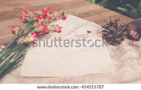 Cute stuff (nut red carnation flower, white plate and mobile phone) on wooden background.craft mock up set with vintage effect and low light.