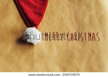 cute stylish christmas red hat on a beautiful craft holiday wrapping paper, winter holidays, merry christmas text - stock photo