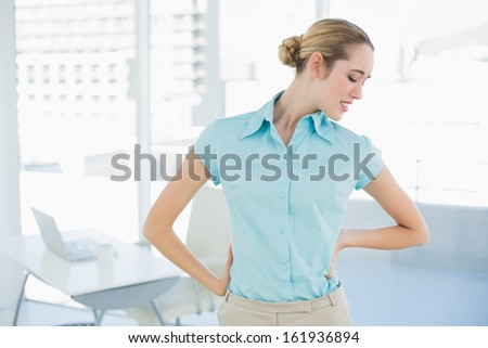 Cute suffering businesswoman holding her injured back standing in her office