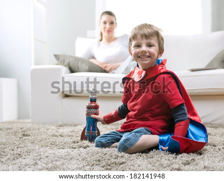 Cute superhero boy paying with toy rocket in the living room with his mother on background. - stock photo
