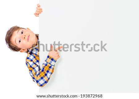 Cute surprised boy peeking out from behind a white board. Copy space. Isolated over white. - stock photo