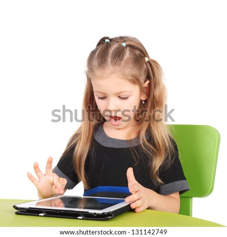cute surprised little girl playing with the tablet PC