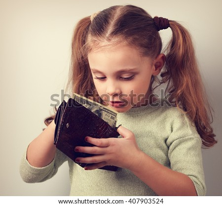 Cute surprising small kid girl looking in mother wallet and want to take money. Toned closeup portrait - stock photo