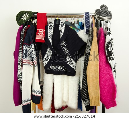 Cute sweaters with snowflakes displayed on a rack. Wardrobe with colorful winter clothes and accessories. - stock photo