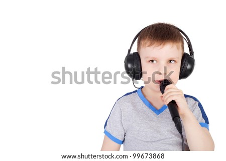 cute sweet little boy in the headphones with the microphone singing karaoke