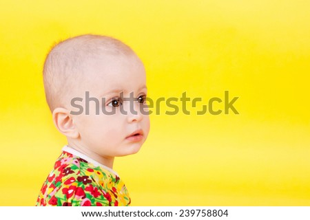 cute sweet little child sitting on the yellow background